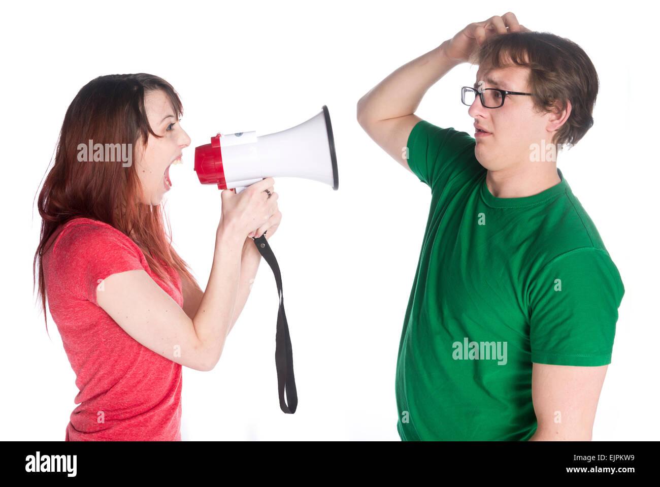 La donna grida al suo uomo con Megafono Immagini Stock