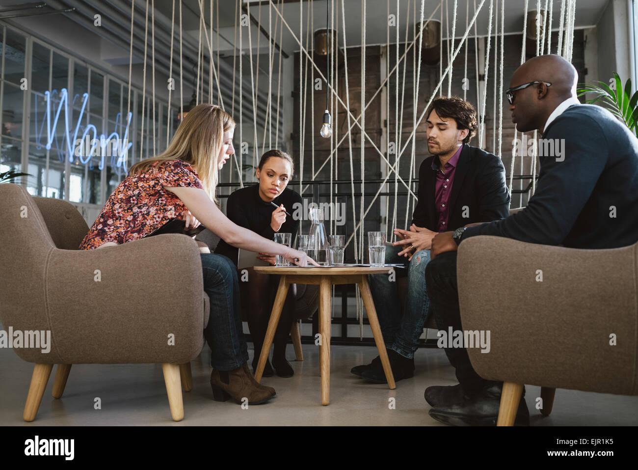 Diversi gruppi di dirigenti riuniti in ufficio condividendo idee creative. I giovani aventi un incontro nella lobby. Immagini Stock