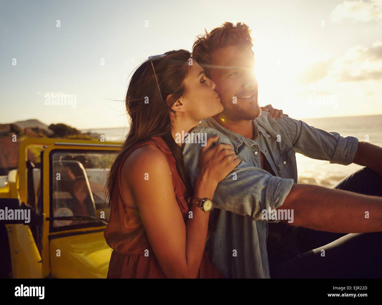 Romantico coppia giovane seduto sul cofano della loro auto mentre su roadtrip. Bella giovane donna baciare il suo Immagini Stock