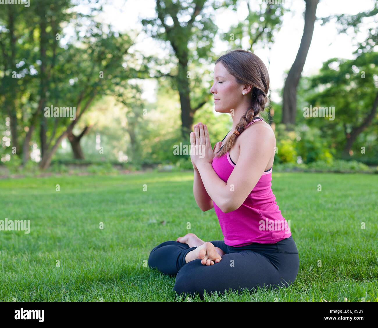 La donna caucasica meditando in posizione di parcheggio Immagini Stock