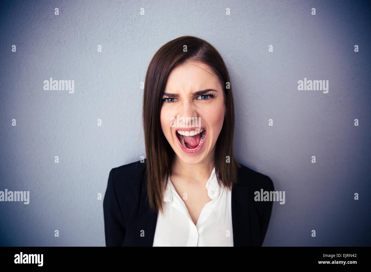 Imprenditrice arrabbiato grida su sfondo grigio. Guardando la fotocamera Immagini Stock