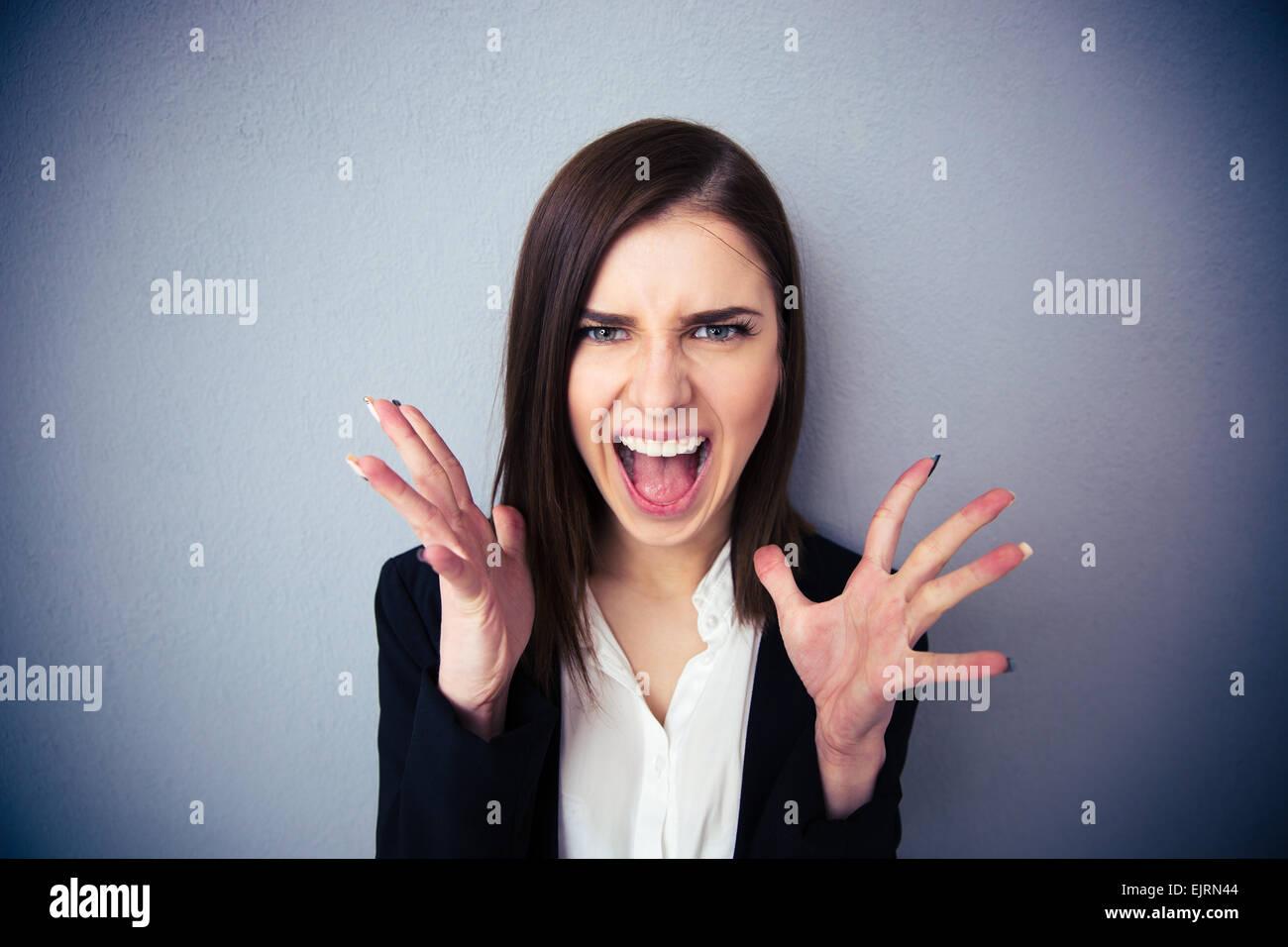 Arrabbiato donna urlando su sfondo grigio. Guardando la fotocamera Immagini Stock