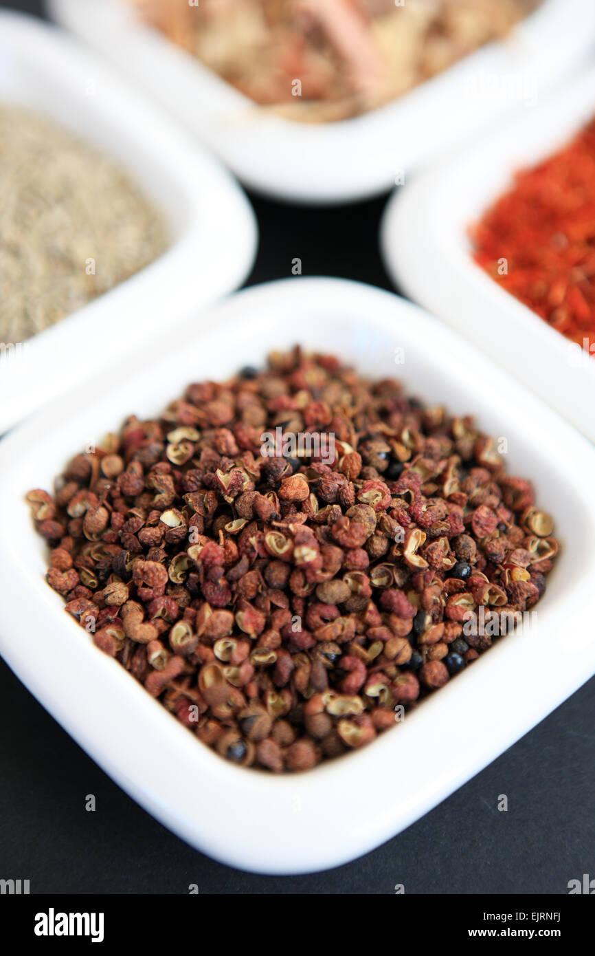 Pepe Szechuan con, in senso orario a partire da grani di pepe, semi di cumino, citronella e zafferano nei piatti Immagini Stock