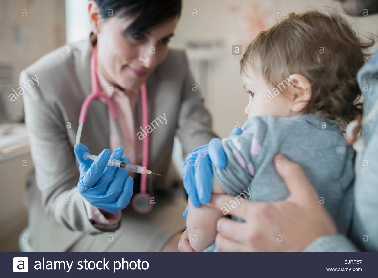 Pediatra dando bambina la vaccinazione in clinica Immagini Stock