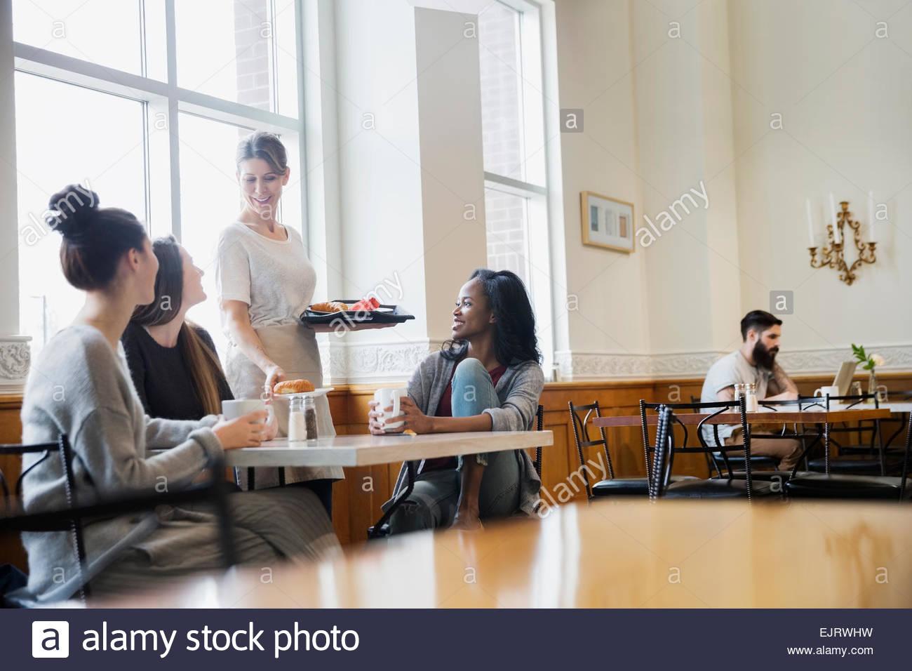 Donna che serve gli amici presso il cafe tabella Immagini Stock