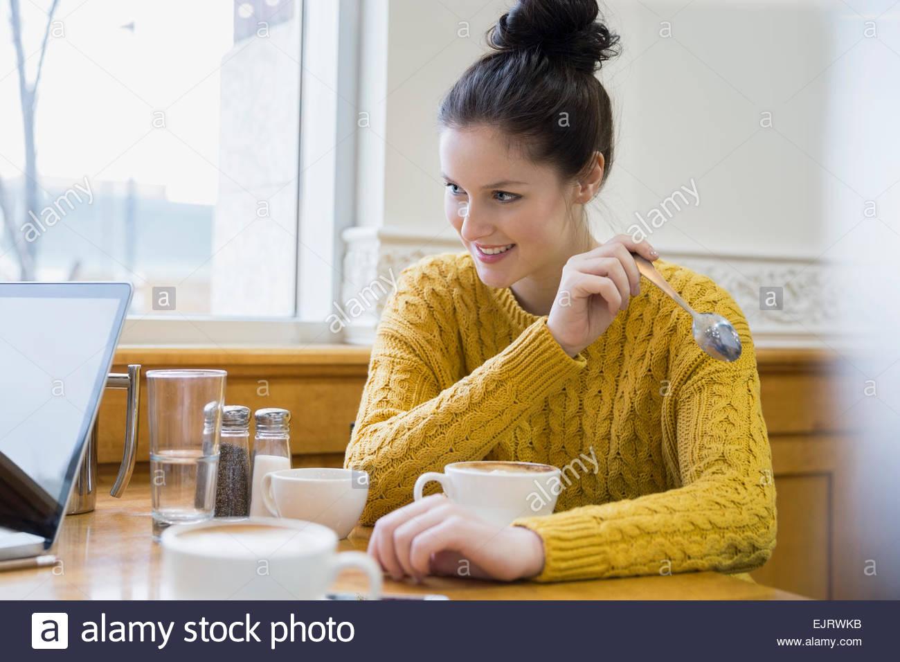 Donna sorridente bere cappuccino in cafe Immagini Stock