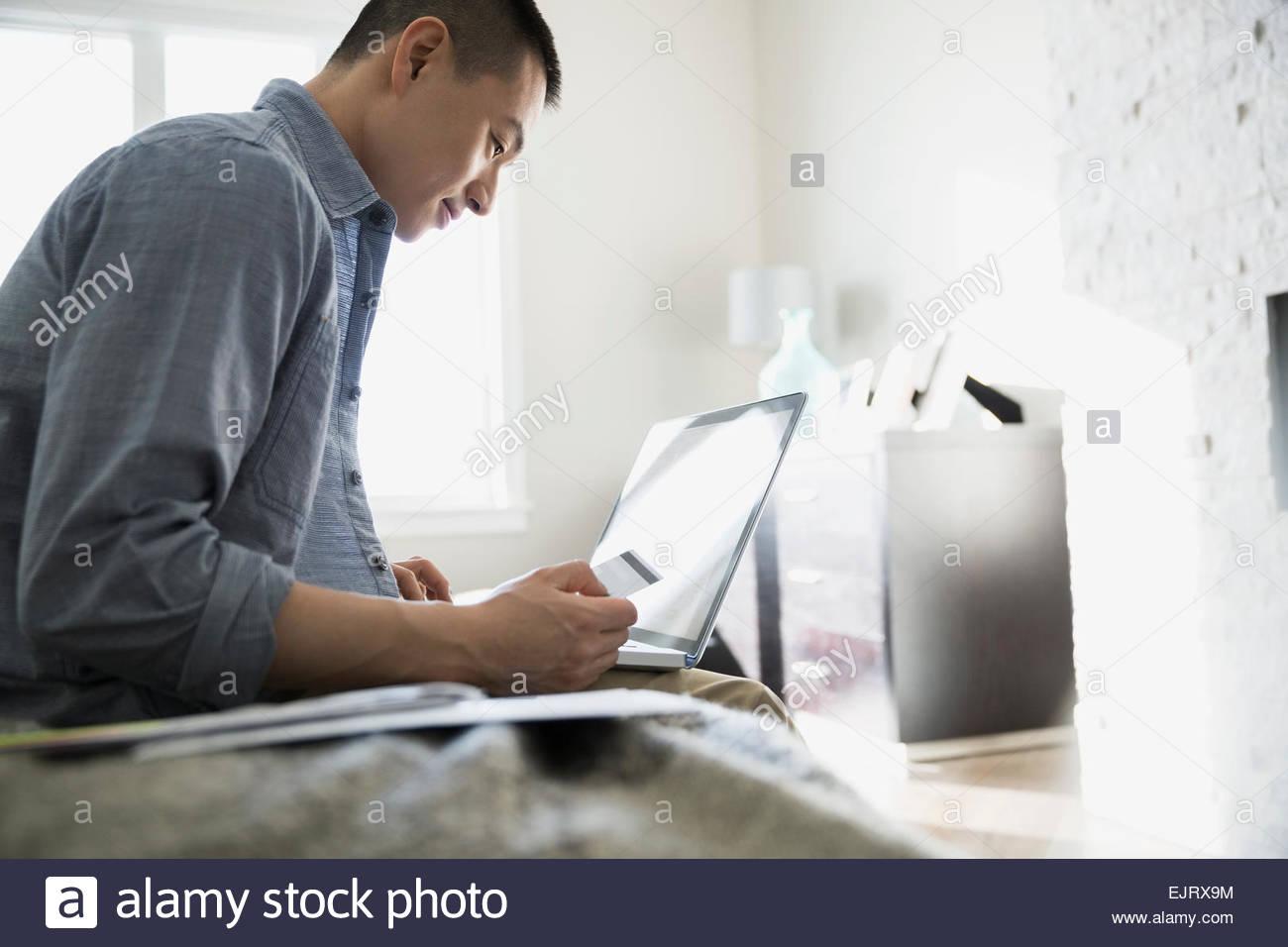 L uomo lo shopping online con carta di credito e il computer portatile Immagini Stock