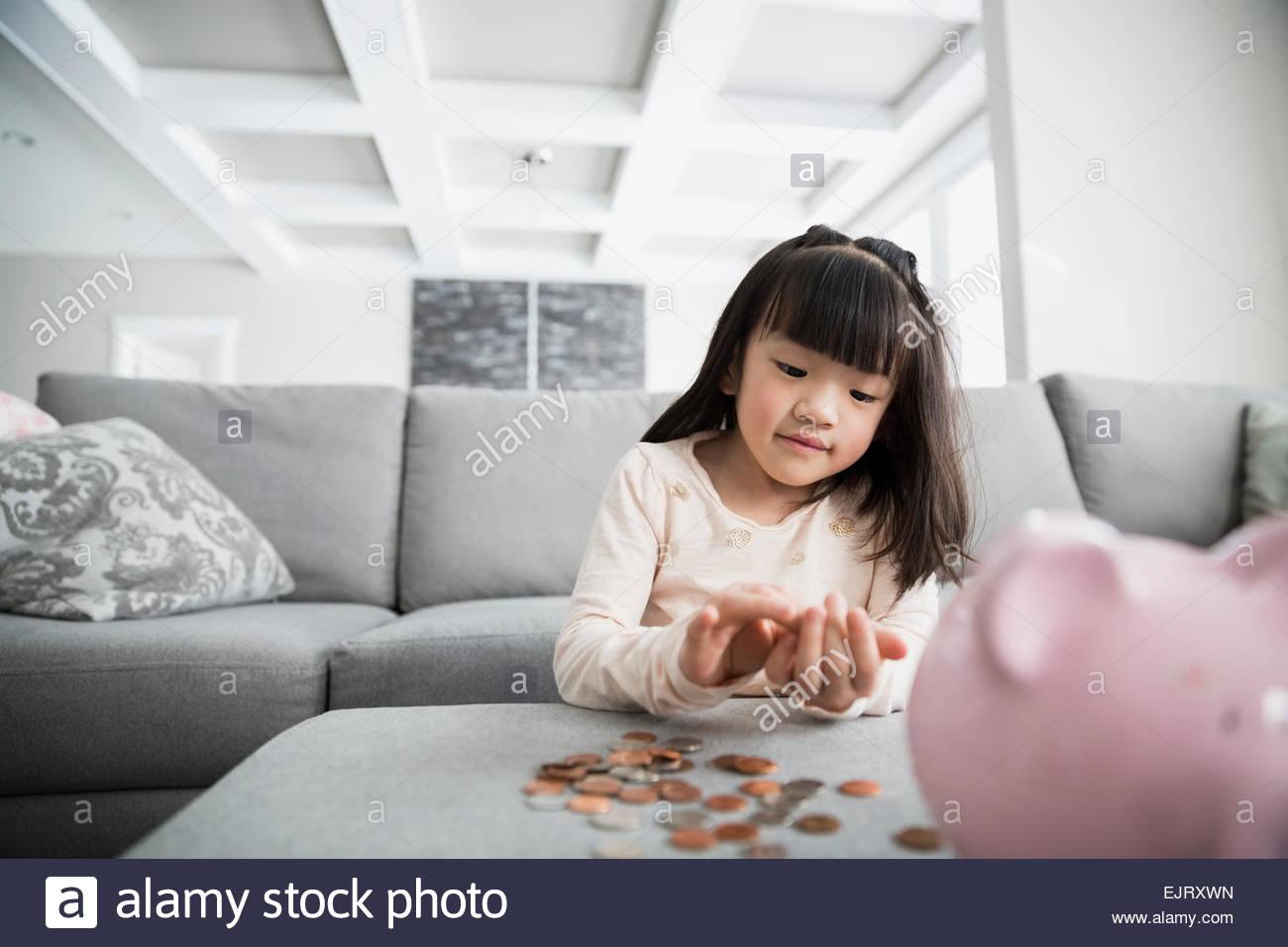 Ragazza il conteggio delle monete dal salvadanaio in salotto Immagini Stock