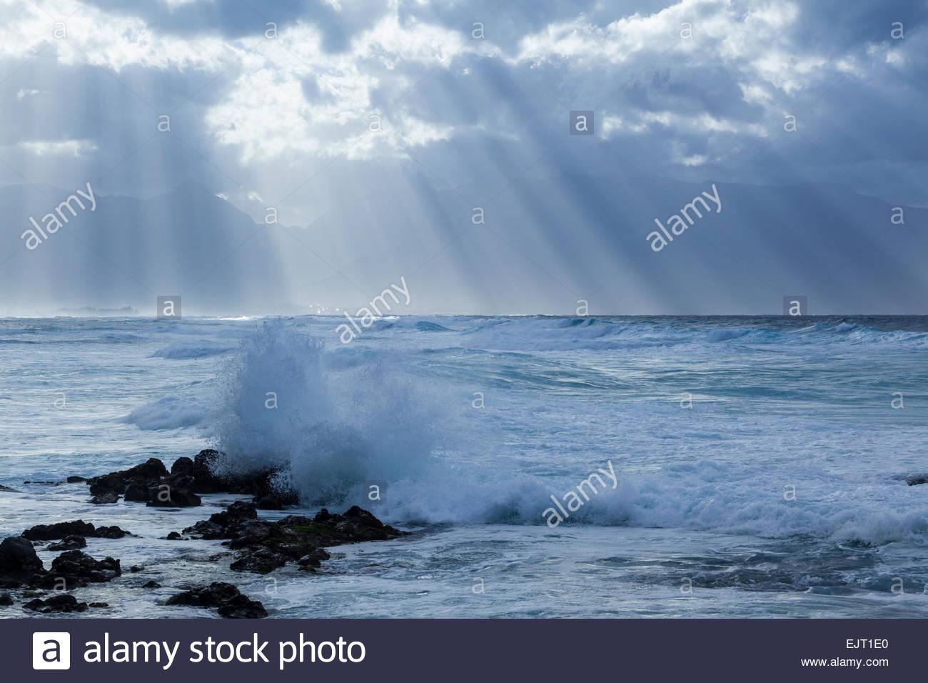 Raggi crepuscolari, stratocumulus nuvole e surf a Hookipa Bay sull'isola di Maui nello stato delle Hawaii USA Immagini Stock
