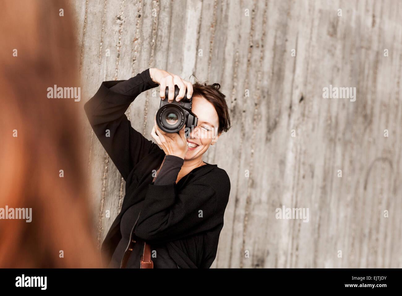 Donna felice fotografare amico contro la parete Immagini Stock