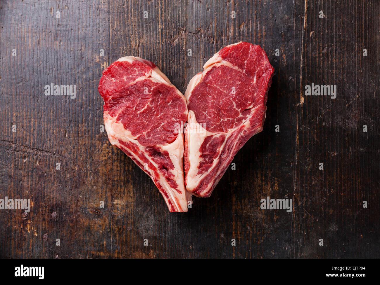 Forma di cuore la carne cruda Ribeye entrecote su sfondo di legno Immagini Stock
