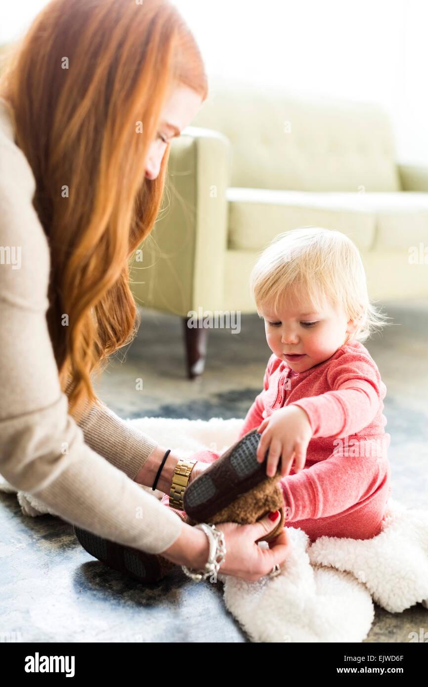 Medicazione di madre figlio (2-3) in soggiorno Immagini Stock