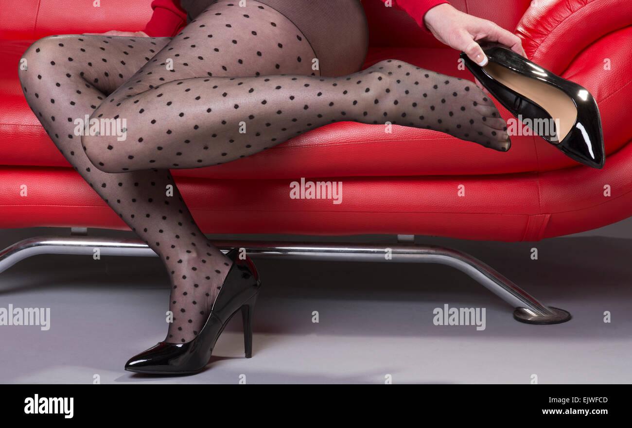 Divano Rosso E Nero : Donna seduta su un divano rosso vestita di nero macchiato il