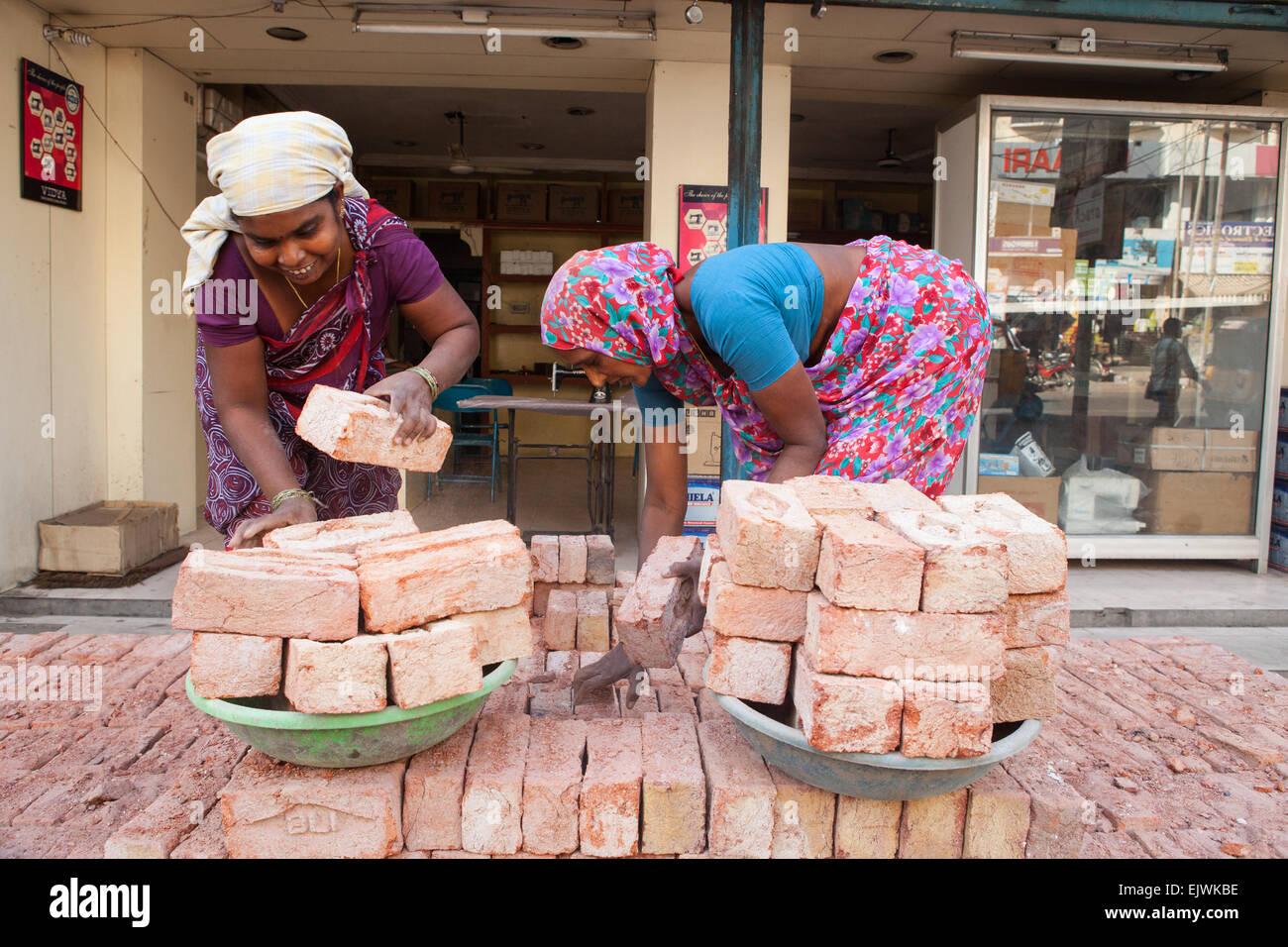 Donne pila mattoni su di loro hods in Hyderabad Immagini Stock