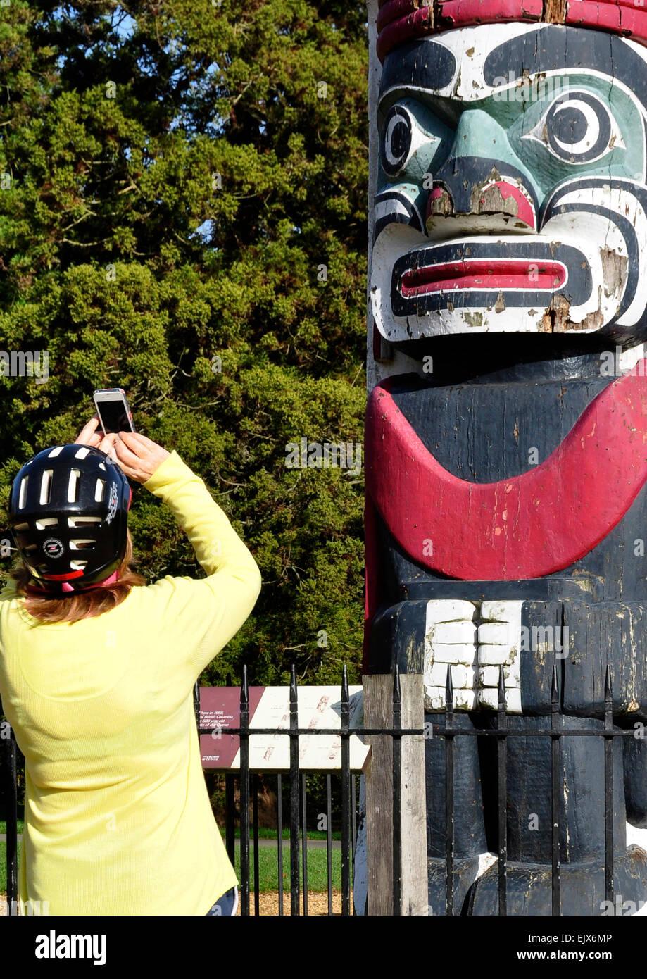 Donna che indossa il casco ciclo - utilizzo di digital phone per fotografare tribale intagliato faccia su legno Foto Stock