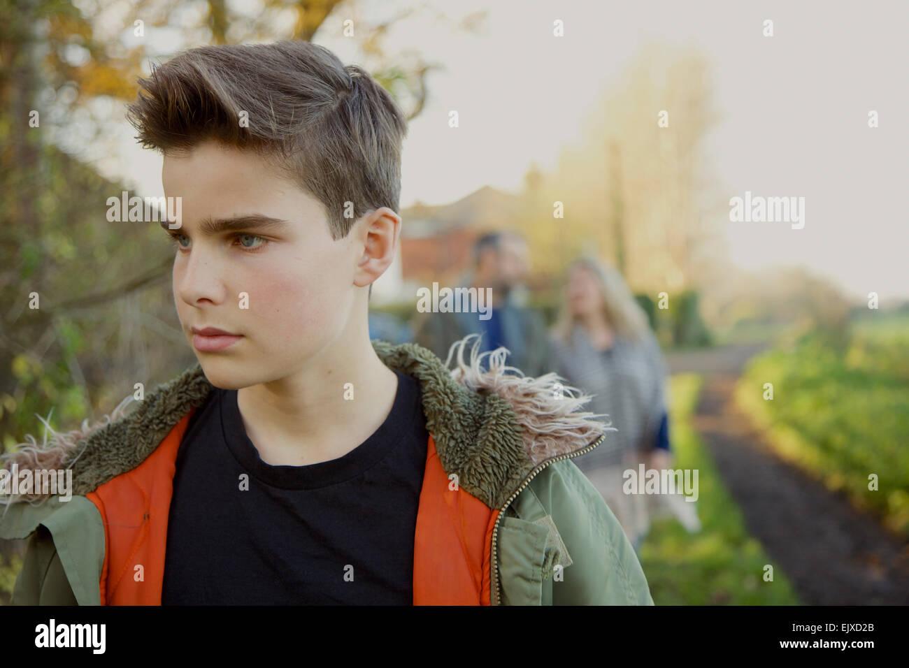 Ragazzo adolescente a piedi nella strada di campagna, i genitori in background Foto Stock