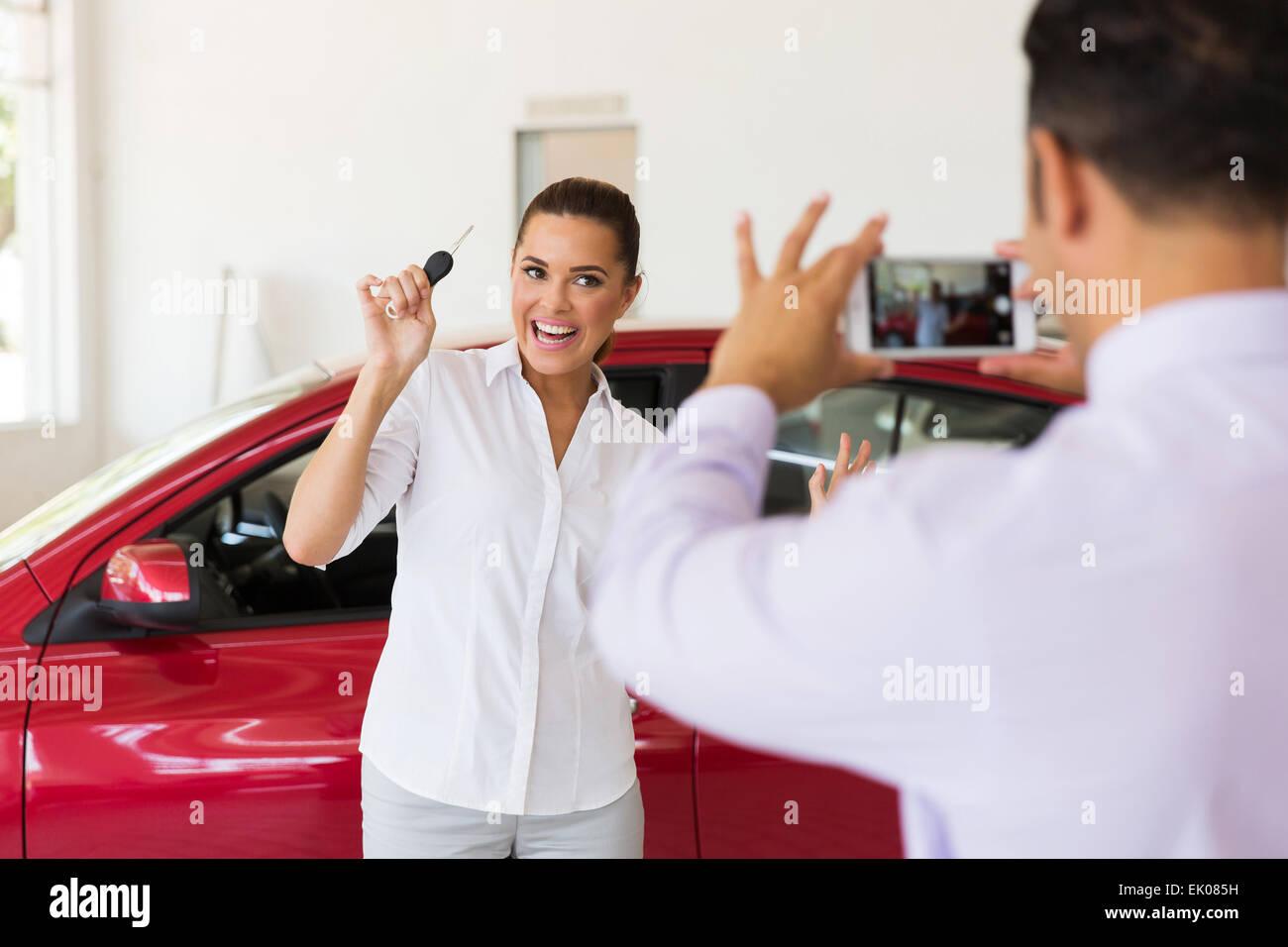 Venditore di scattare una foto del Excited donna accanto alla sua nuova vettura in showroom Foto Stock