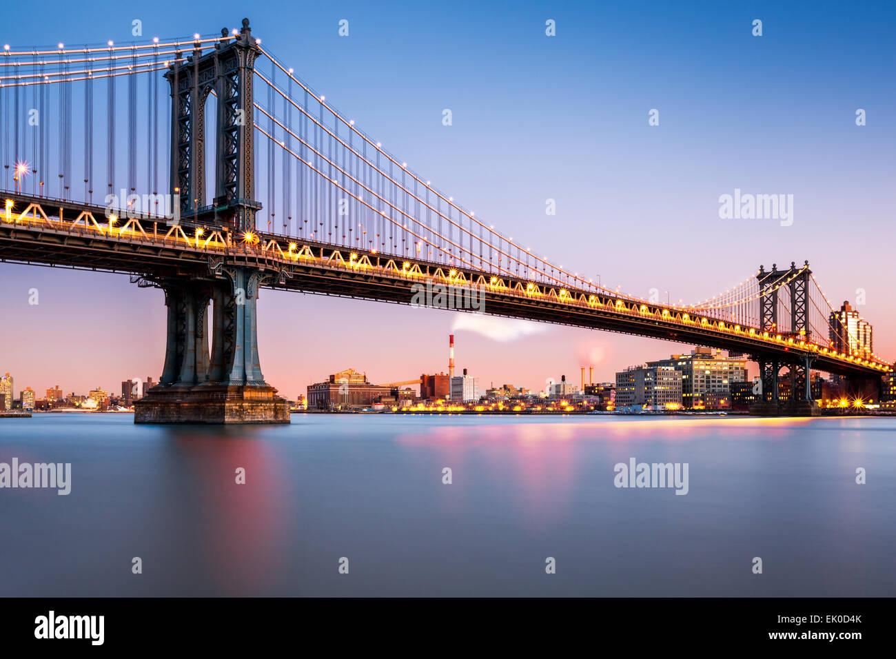 Manhattan Bridge illuminato al crepuscolo (molto lunga esposizione per una superficie perfettamente liscia acqua) Immagini Stock