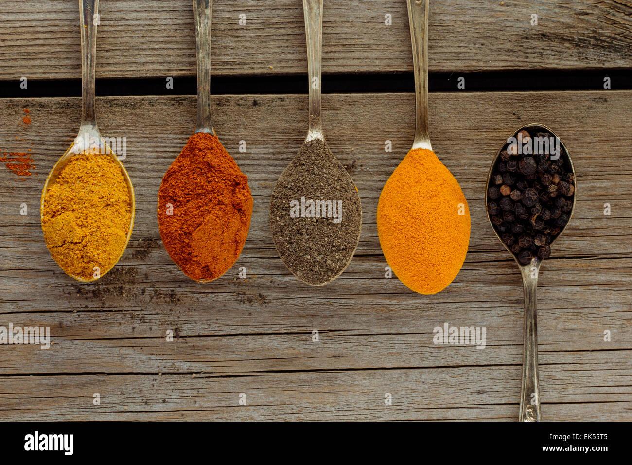 Curry, nero e peperoni rossi, Peppe e curcuma su cucchiai vista superiore Immagini Stock