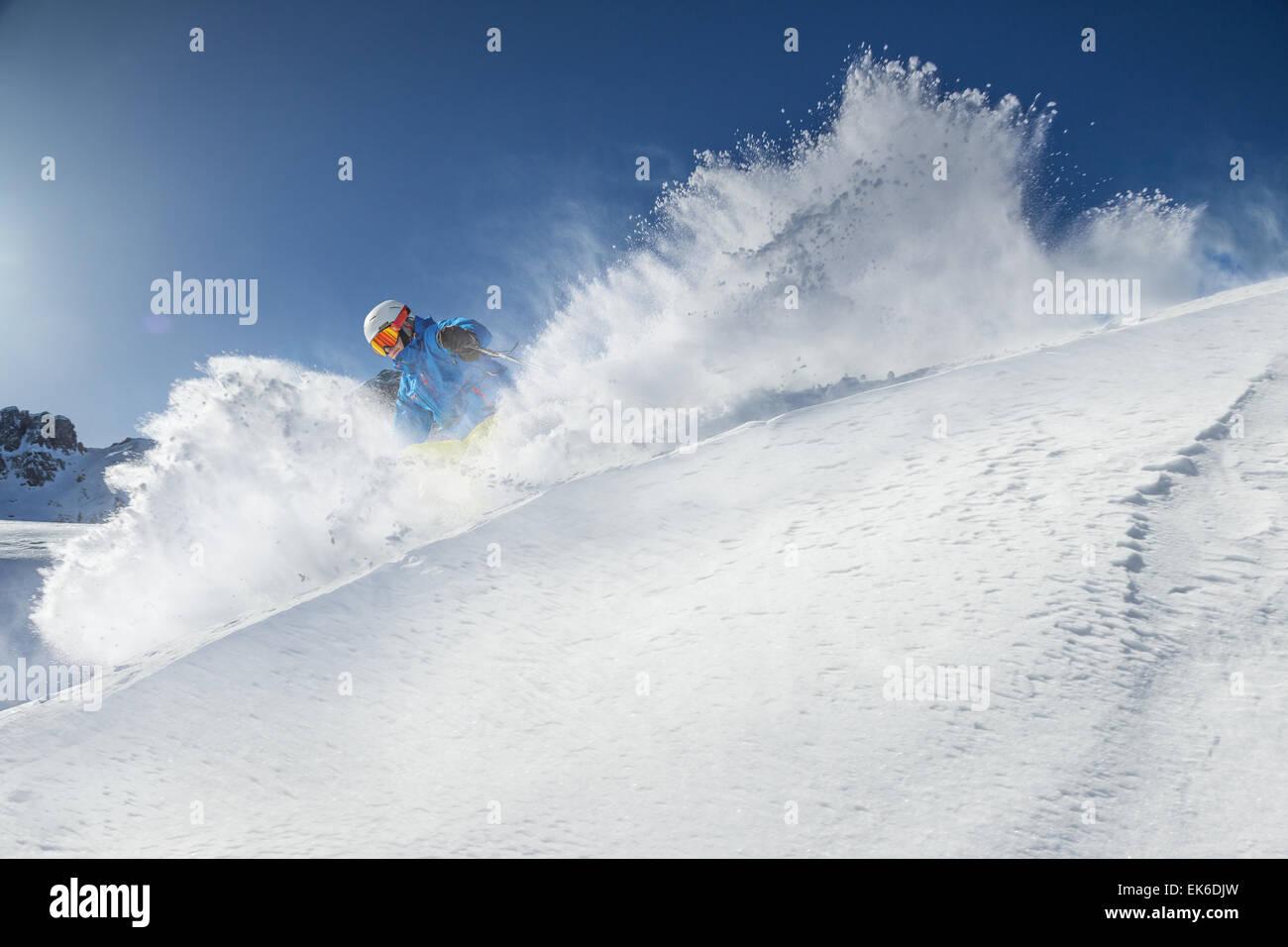 Sciatore in discesa sugli sci in alta montagna durante la giornata di sole. Immagini Stock