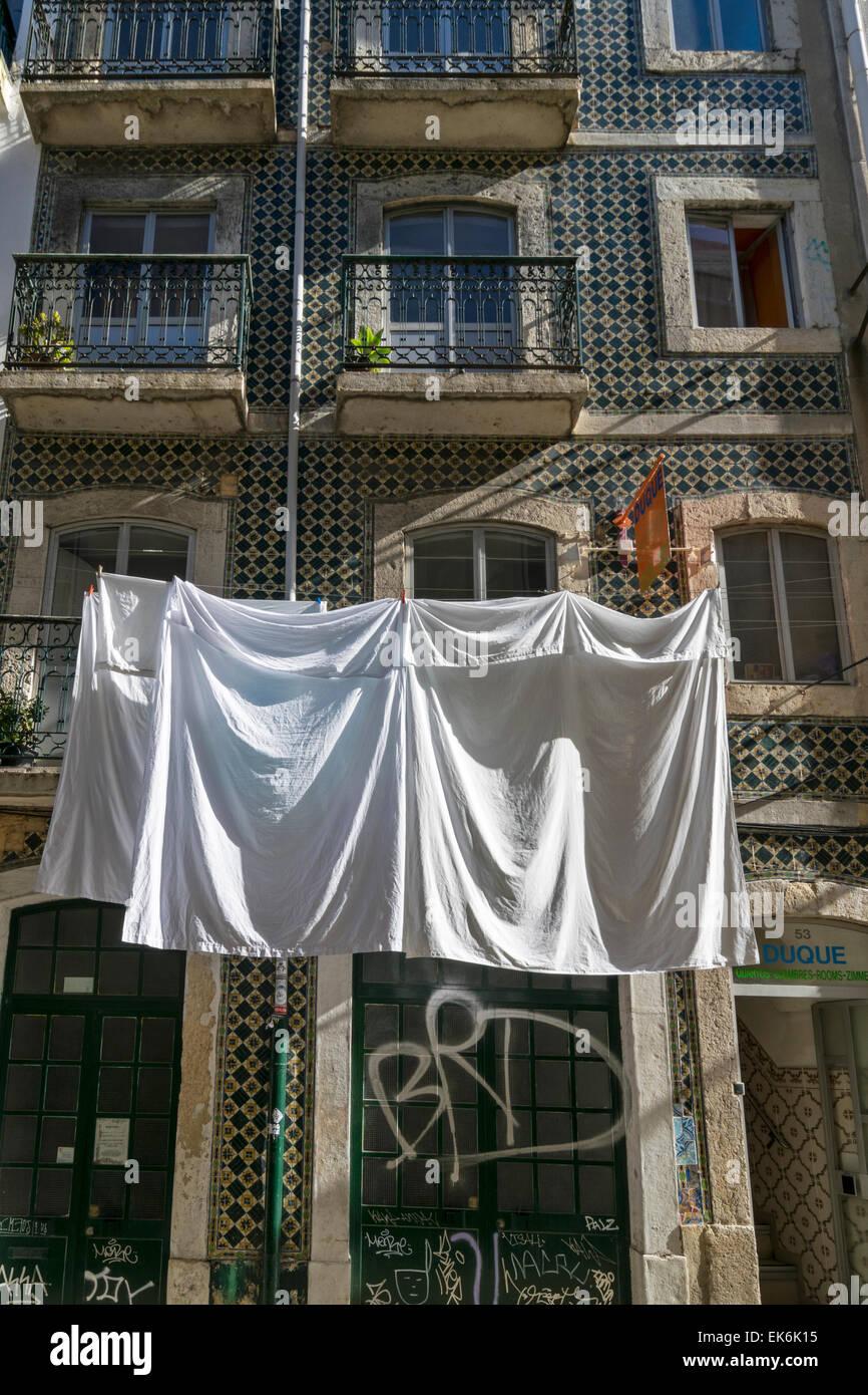 Lisbona portogallo lenzuola appesi ad asciugare al di fuori di un vecchio edificio piastrellato nel centro della Immagini Stock