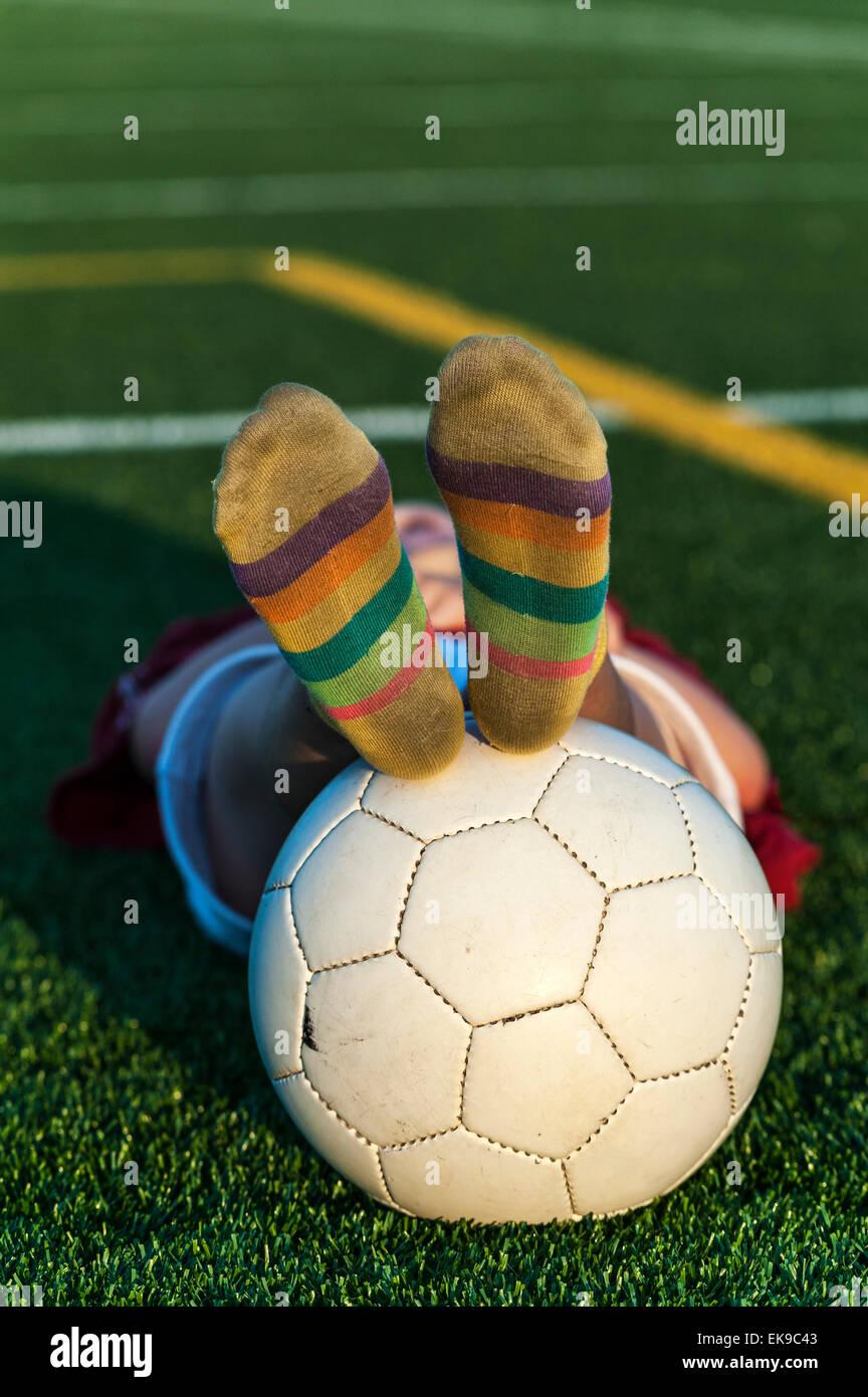 Stanco della bambina con pallone da calcio dopo la pratica. Immagini Stock