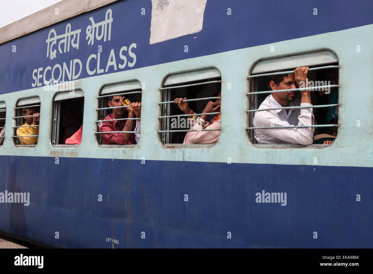 I passeggeri in una seconda classe carrozza ferroviaria in India Immagini Stock