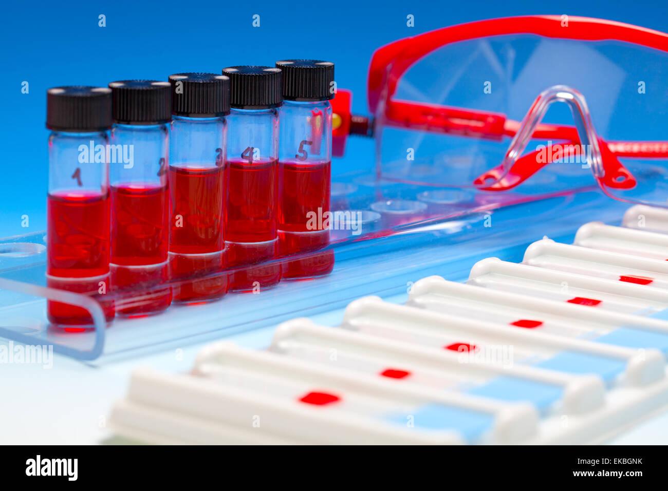 Array di campioni di sangue per microscopia e biopsia di tessuto su blu Immagini Stock