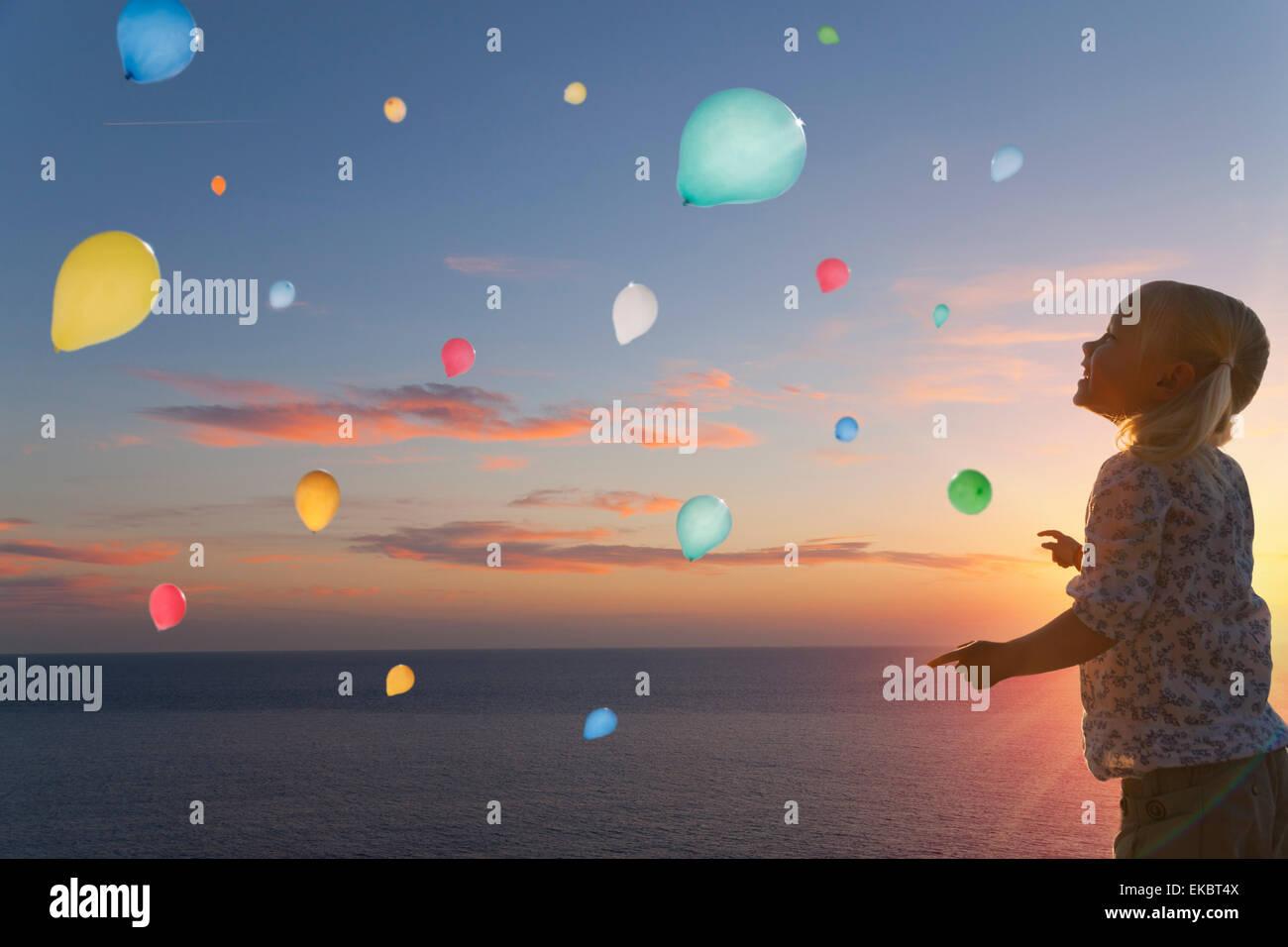 Ragazza guardando palloncini fluttuante nel cielo di sera Immagini Stock