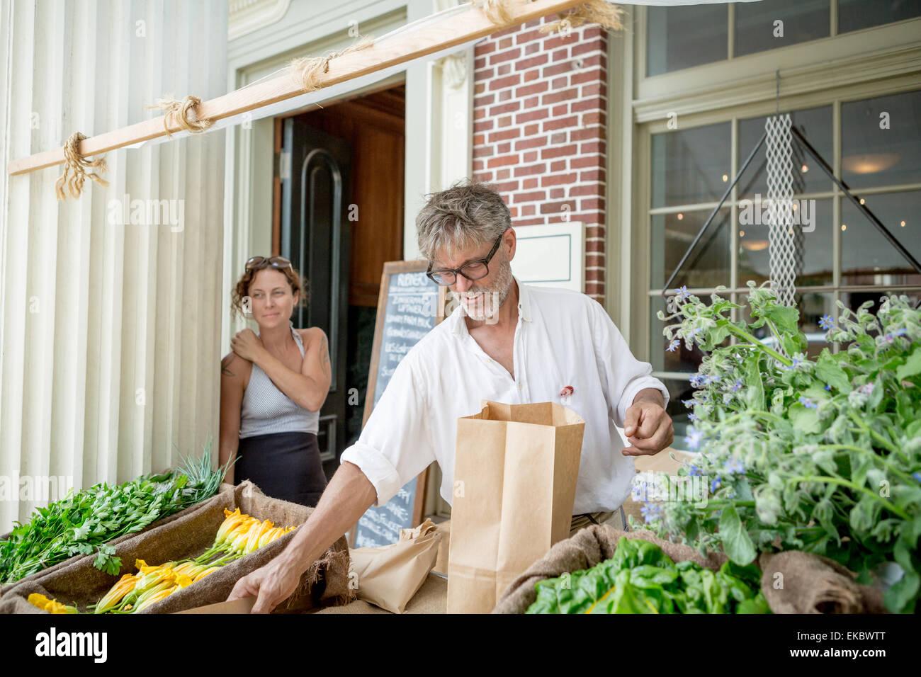 Agricoltore la vendita di alimenti biologici in stallo al di fuori del negozio Immagini Stock