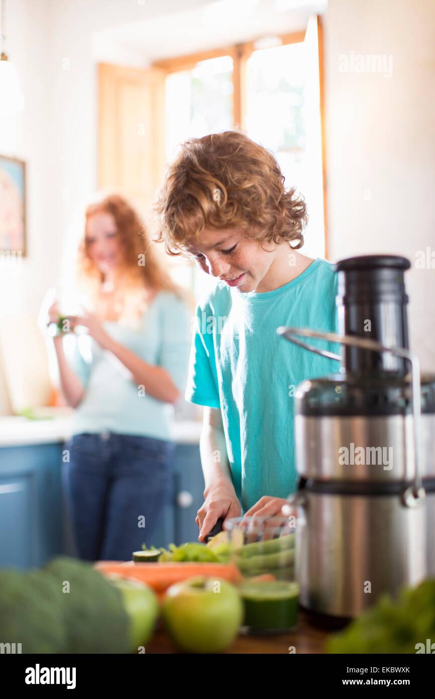 Ragazzo adolescente come tagliare le verdure in cucina Immagini Stock