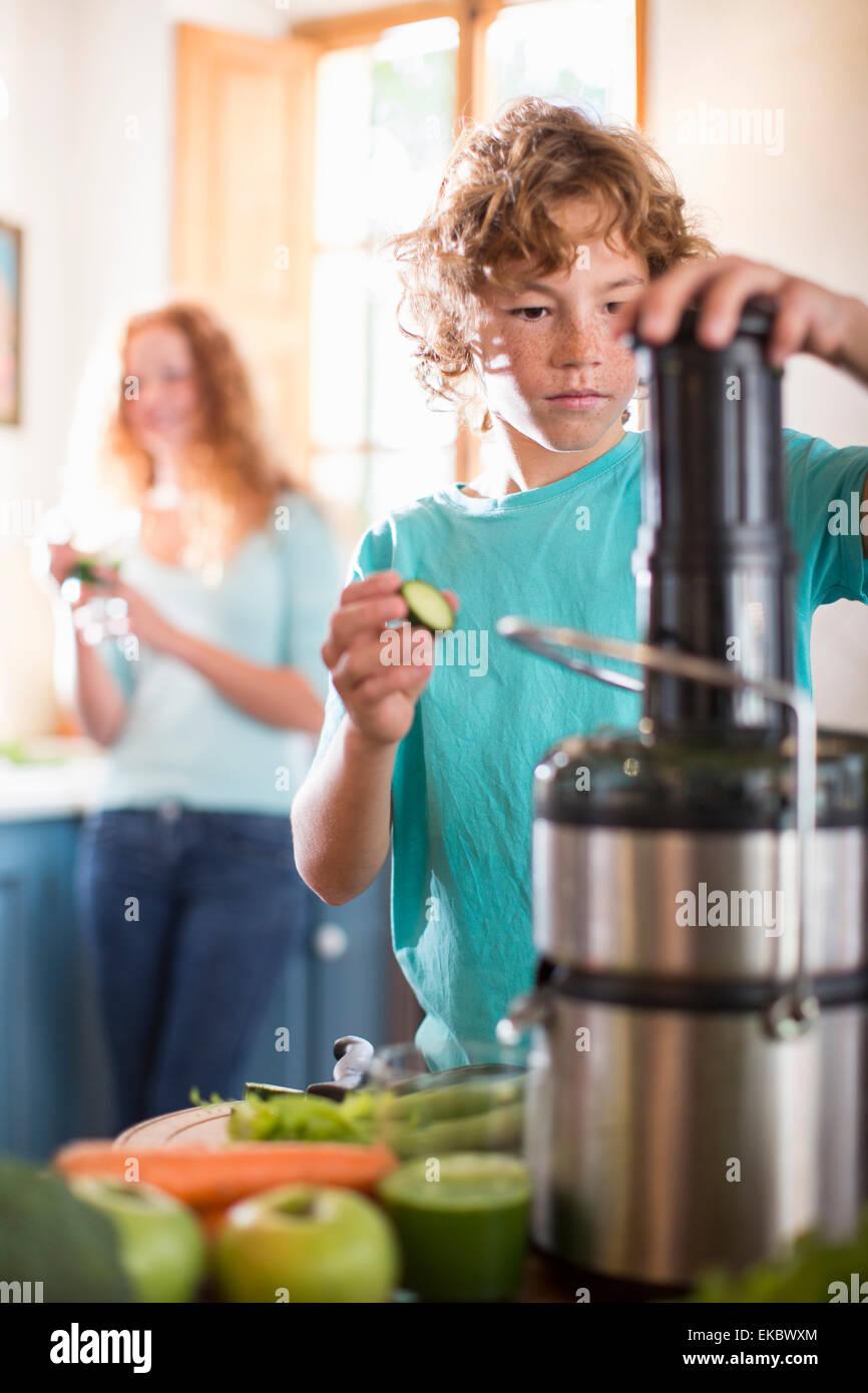 Ragazzo adolescente frutto di miscelazione in cucina Immagini Stock