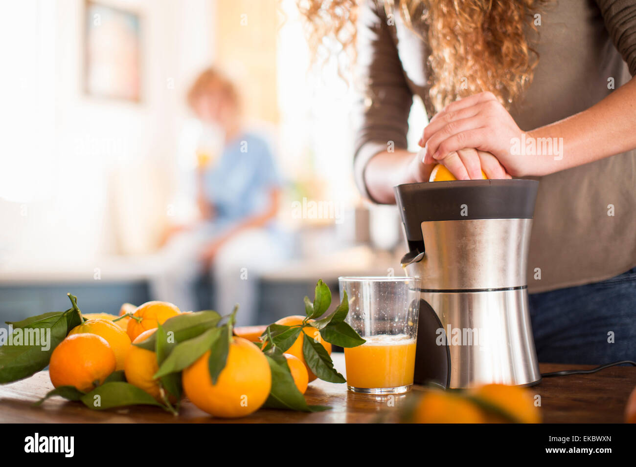 Ragazza adolescente a spremere il succo arancia in cucina Immagini Stock