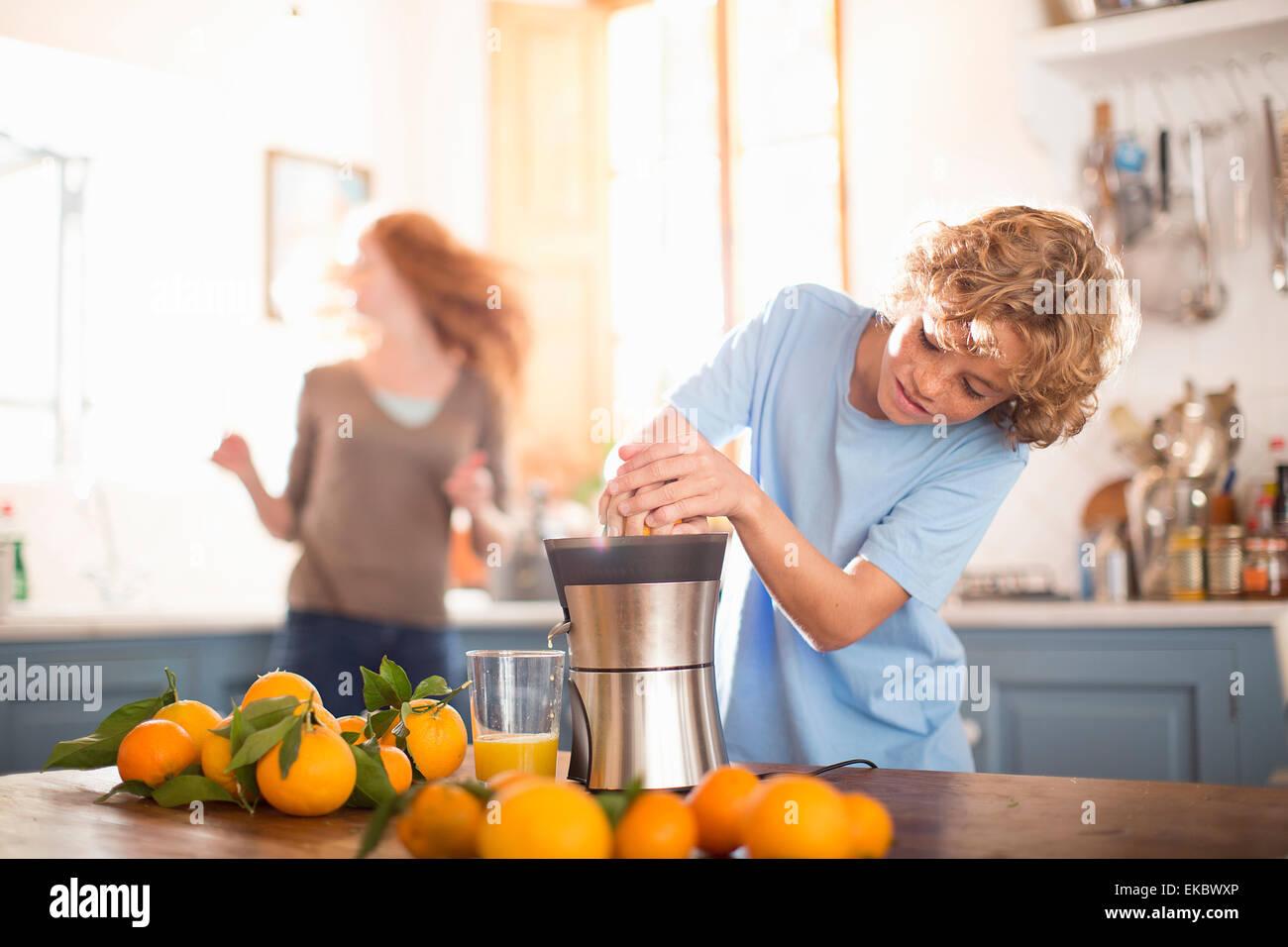 Ragazzo adolescente a spremere il succo arancia in cucina Immagini Stock