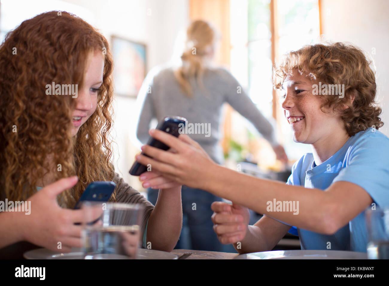 I fratelli utilizza lo smartphone al tavolo da pranzo Immagini Stock