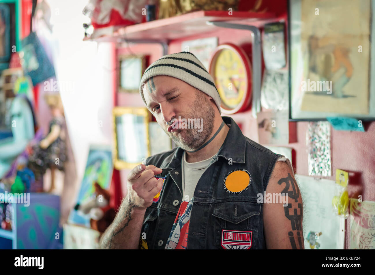 Ritratto di punk maschio negoziante winking in giocattolo vintage shop Immagini Stock