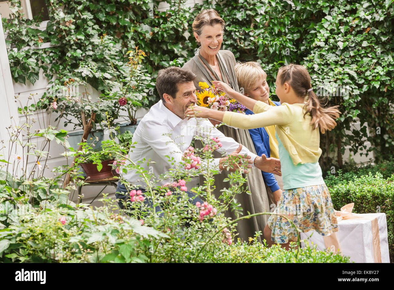 Coppia matura saluto nipoti in giardino Immagini Stock