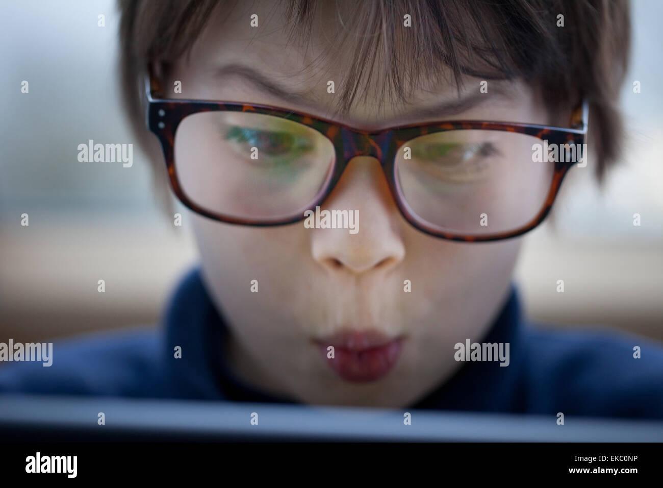 Close up boy tirando una faccia con tavoletta digitale Immagini Stock