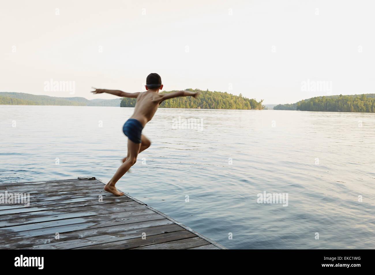 Ragazzo saltando nel lago dal molo in legno, Ontario, Canada Immagini Stock