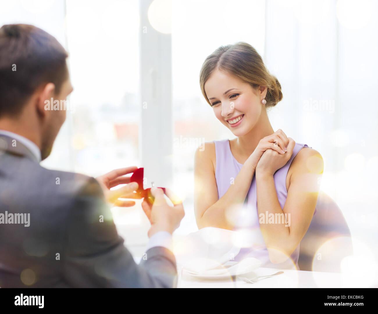 Eccitato giovane donna guardando il fidanzato con anello Immagini Stock