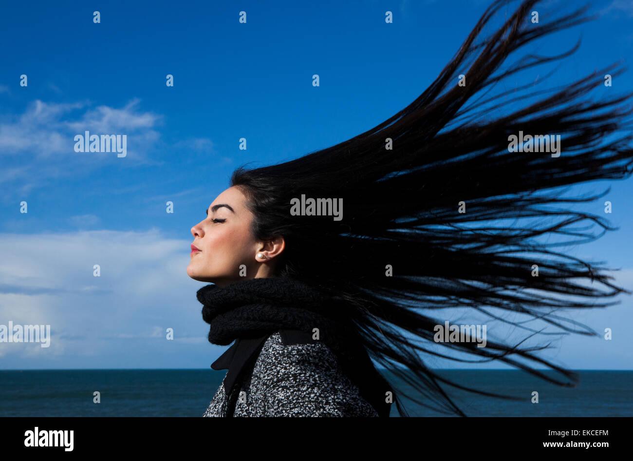 Giovane donna con i capelli al vento Immagini Stock