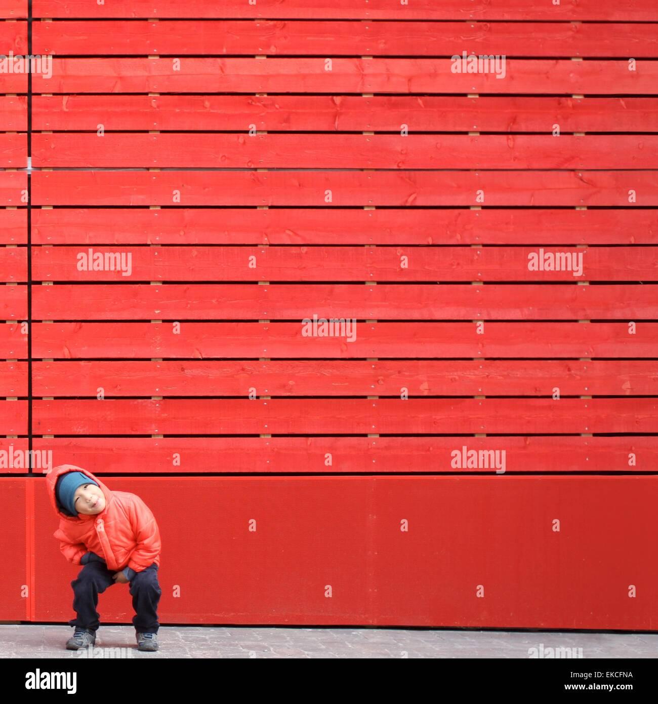 Ragazzo in rosso a giocare davanti a una parete rossa Immagini Stock
