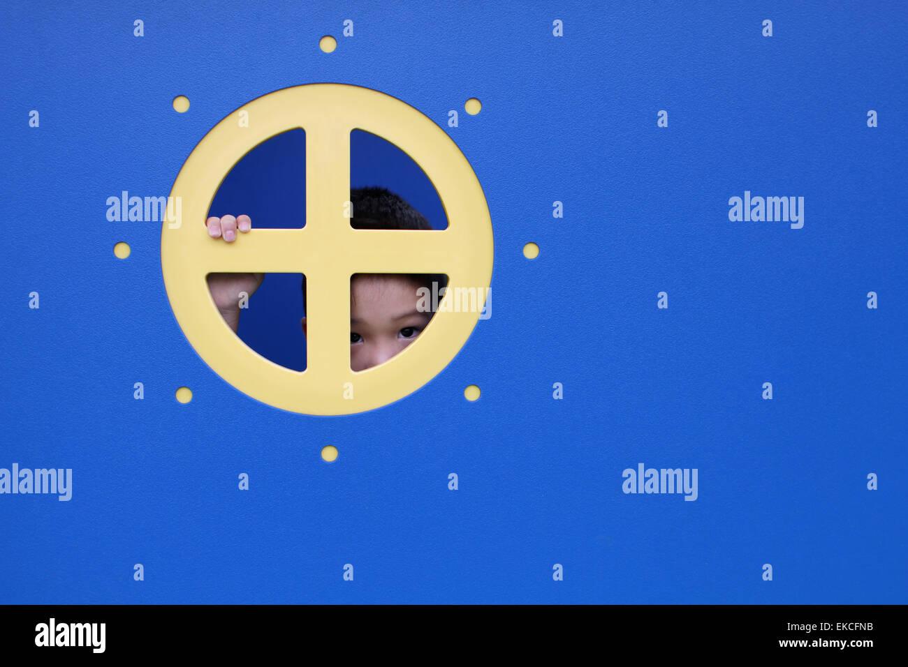 Ragazzo spiata attraverso la finestra rotonda di playhouse Immagini Stock