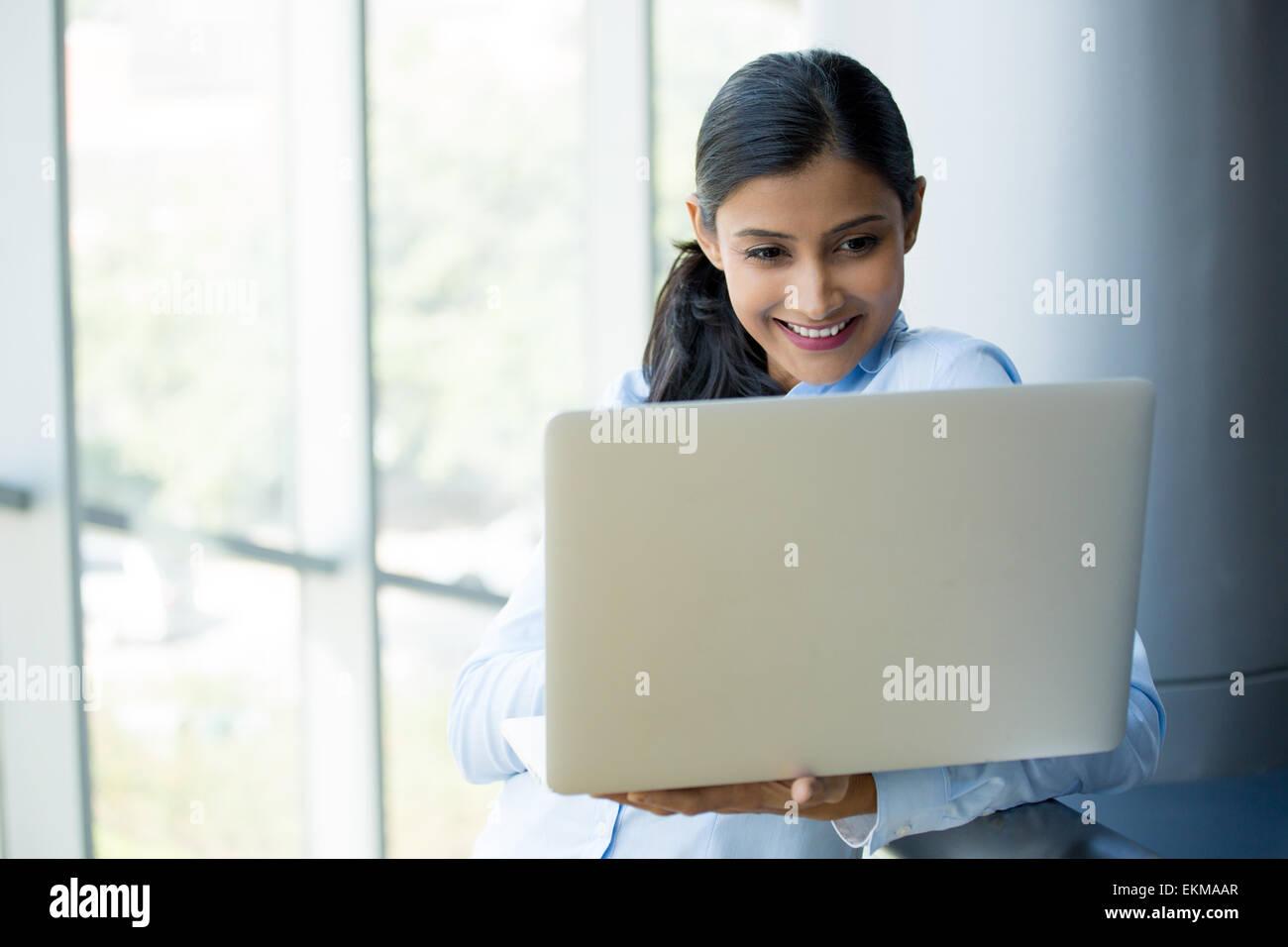 Closeup Ritratto, giovane, attraente moglie, madre, piedi, sorridente alla ricerca, navigazione portatile d'argento. Immagini Stock