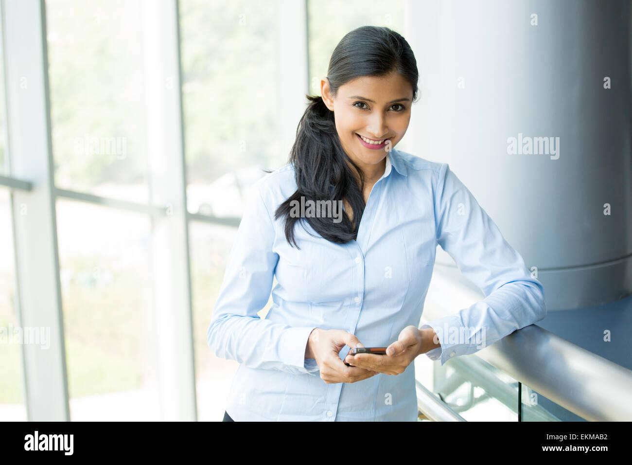 Closeup ritratto, gioiosa donna gorgeous utilizzando lo smartphone mobile device, isolato in interni sullo sfondo Immagini Stock