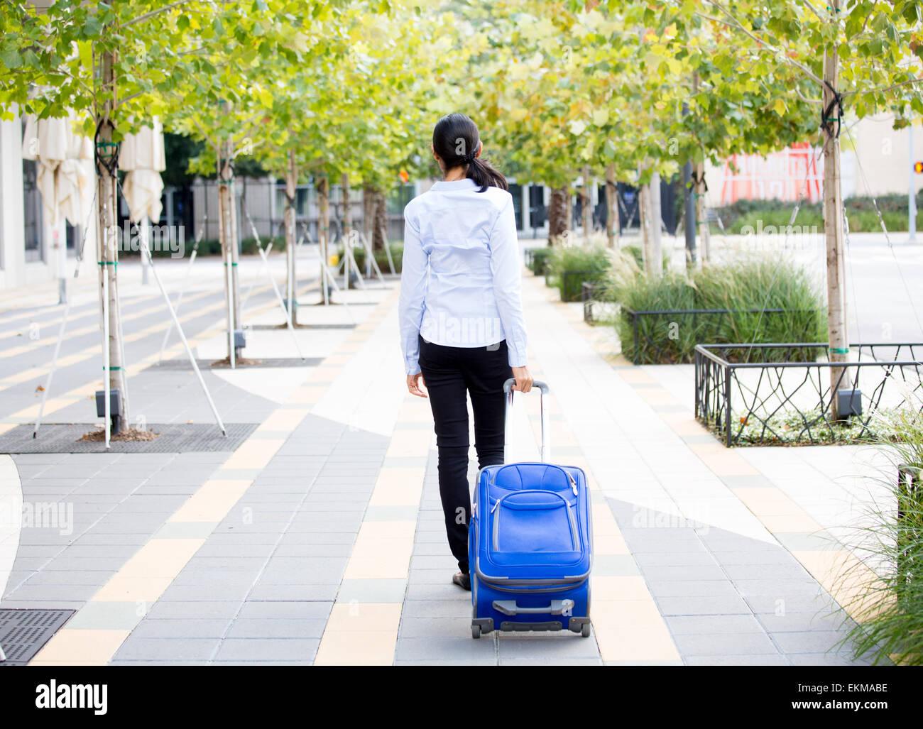 Closeup abstract vista dal retro ritratto di donna in luce maglietta blu che trasportano bagagli, camminando attraverso Immagini Stock