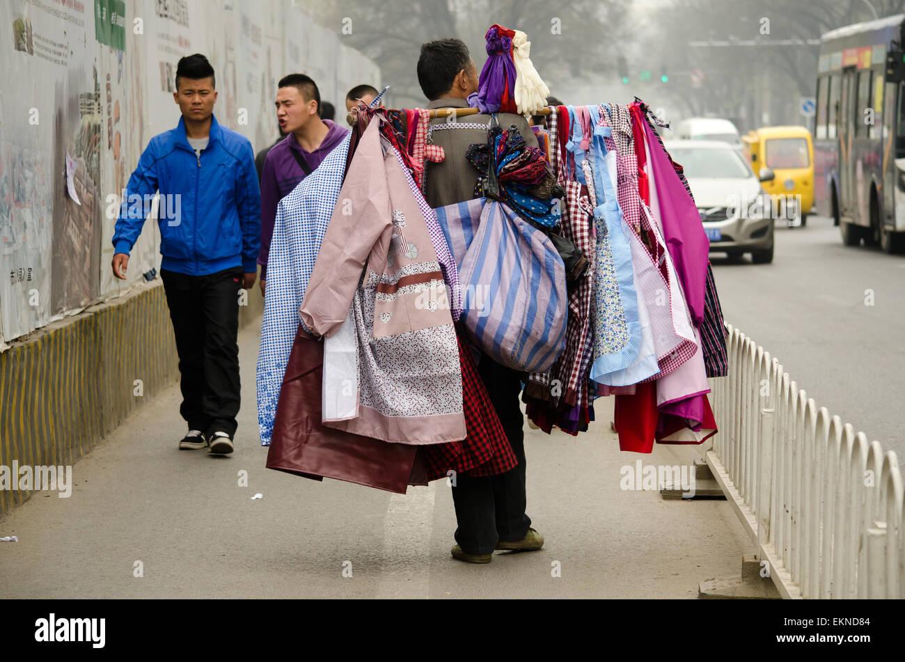 Il vecchio uomo che cammina per le strade che vendono vestiti e tessuti in  Xi an 5ef95069b27