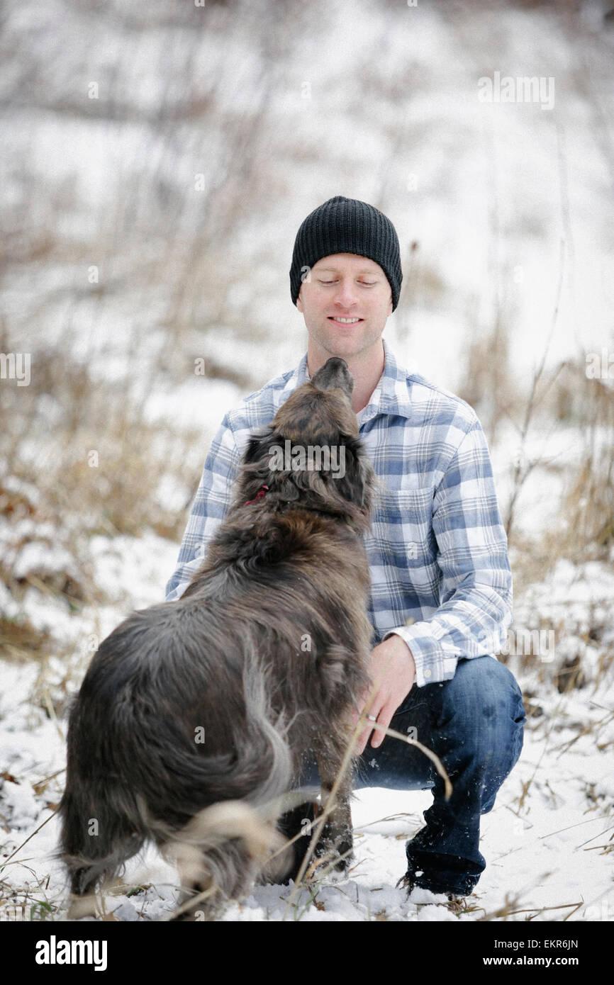 Un uomo in un controllato shirt saluto e pacche un cane. Immagini Stock