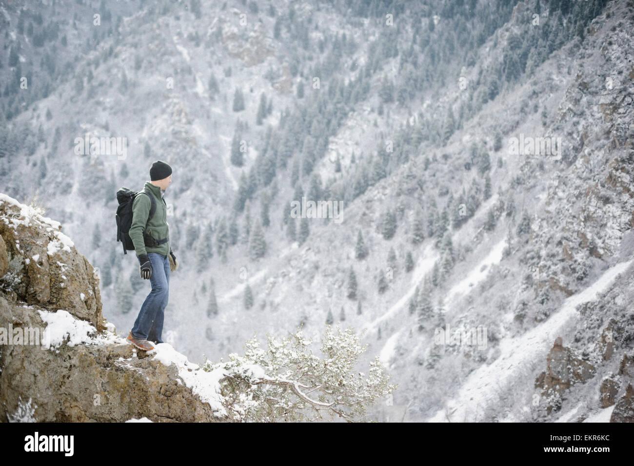 Un uomo in montagna in piedi che guarda in una valle. Immagini Stock