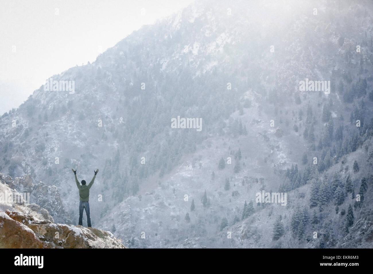 Un uomo salutare il sole, con le braccia sollevate su uno sperone di roccia in montagna. Immagini Stock